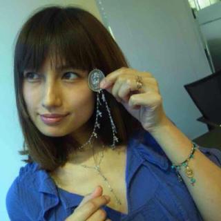ネックレスを持っているブルーの服を着た佐田真由美の画像