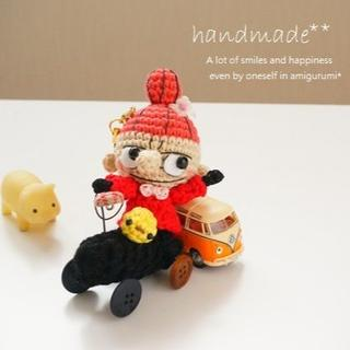 四輪のおもちゃに乗って遊ぶ北欧の女の子*ストラップ(あみぐるみ)