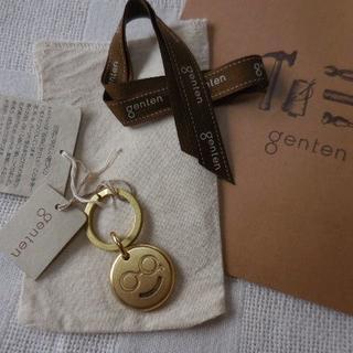 ゲンテン(genten)の新品タグ付 ゲンテン ロゴ入 真鍮 キーホルダー スマイル リボン紙袋保管袋(キーホルダー)