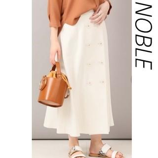 ノーブル(Noble)のボタンサーキュラーラップスカート 白(ひざ丈スカート)