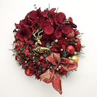 クリスマス 赤い蘭の花に金色トナカイのいる輝きのリース
