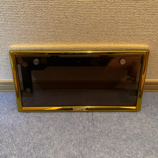 ダイハツ(ダイハツ)のダイハツ純正 ナンバーフレーム ゴールド ブラウンスモーク 自動車/バイクの自動車(車外アクセサリ)の商品写真